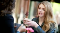 Woman have a chat while enjoying latte.