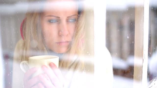 Woman having a tea or coffee on snowy day.