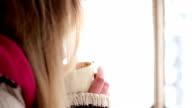 Frau mit einer Tasse Tee oder Kaffee Am verschneiten Tag.