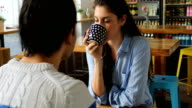 Woman Having Coffee While Talking With Man At Cafe
