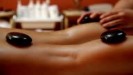 Woman having her legs massaged with hot stones in spa