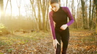 Woman having pain on her knee while jogging.