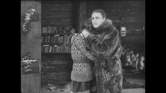 Woman helps man into fur coat before crying sorrowfully on his shoulder