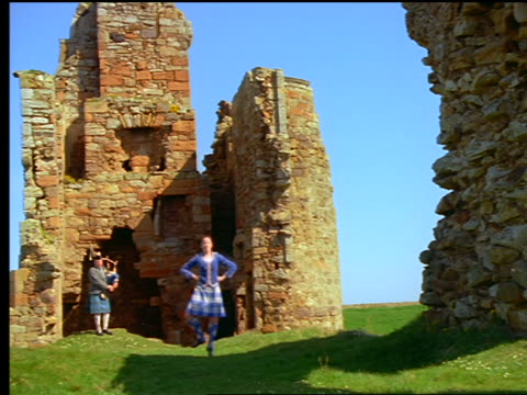 Woman highland dancing + man playing bagpipes near castle ruins / Newark Castle, Scotland