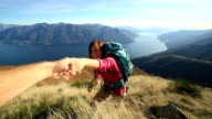 Woman hiker climbing mountain, hand reaches out to help