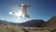 Woman hiker jumping in slow motion from mountain top