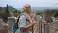 Woman hikes above ruins of ancient Greek civilization