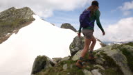 A woman hiking along a ridge in the French Alps in early summer.