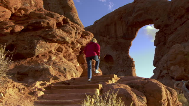 Woman hiking on desert trail towards Turret Arch in the spectacles area