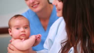Woman holding a baby next to a nurse
