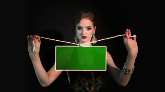 Woman holding a green blackboard