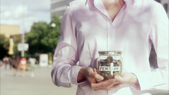 Woman holding a jar full of money, Sweden.