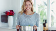 A woman holding a salad colander and smiling to camera