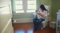 WS Woman holding baby daughter (3-5 months), sitting in rocking chair in nursery / Seattle, Washington State, USA
