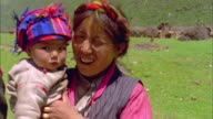 Woman holding baby wearing headscarf winks at camera, Himalayas Available in HD.
