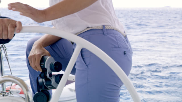 MS Woman holding binoculars while navigating a sailboat
