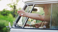 Woman holding hand out of window while driving