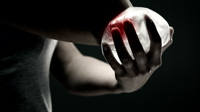 Woman holding ice on painful elbow.