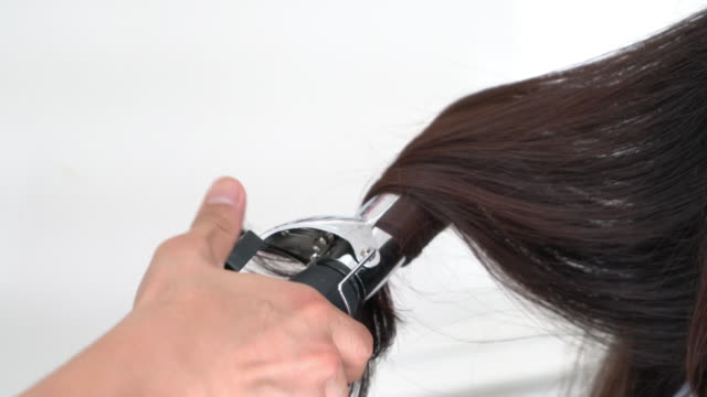 woman holding iron curling hair