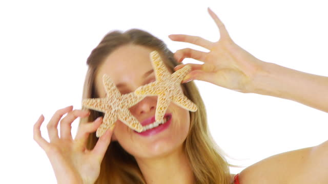Woman holding starfish over eyes