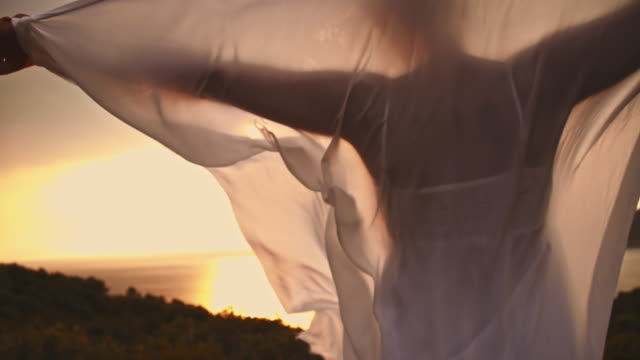 SLO MO Woman holding veil in wind on a coast