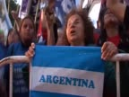 A woman holds an Argentinian flag as she sings in May Square for the celebrations of President Cristina Fernandez' reelection