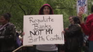 A woman holds up a protest sign 'Regulate Banks not my Birth Control' at the May Day Occupy Wall Street rally in Bryant Park NYC
