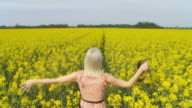 HD SLOW MOTION: Woman Hopping Through Canola Field