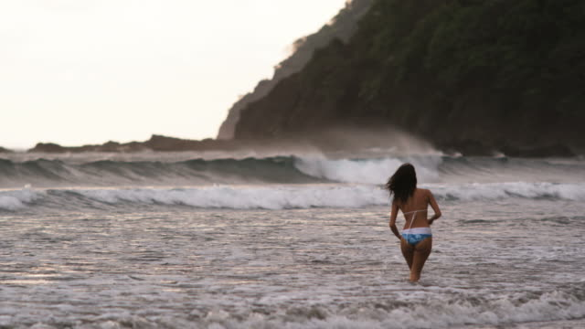 woman in a bikini walking into the surf