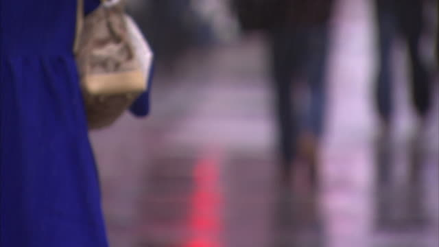 A woman in a blue raincoat carries a handbag and a shopping bag as she walks in the rain.