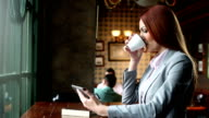 Woman in a cafe using tablet and drink coffee