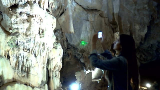 Woman in a Cave taking photos