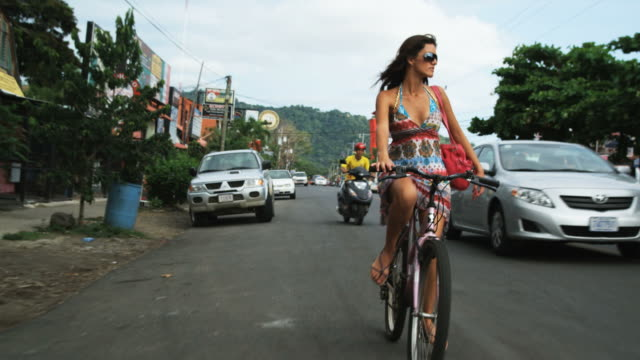 woman in a dress and sunglasses riding a bike down the street