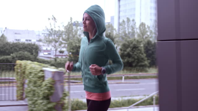 SLO MO TS Woman in a hoodie running along the city street