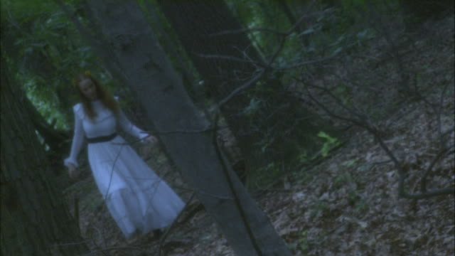 A woman in a long white dress with flowers in her hair walks through a forest.