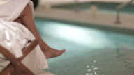Woman in a spa, close up of her legs next to the swimming pool.