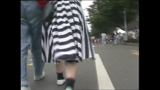 A woman in a striped skirt walks with a friend.