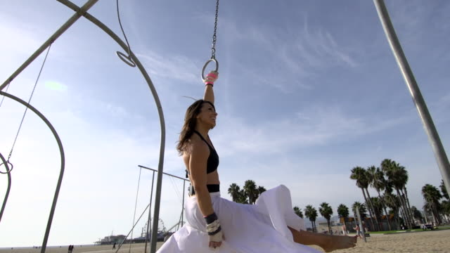 A woman in a white dress swings on traveling rings at Santa Monica beach.  - Slow Motion