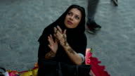 A woman in abaya gets a henna tattoo on the arm at the Arabian market Souq Waqif in Doha, Qatar