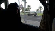 A woman in an abaya drives in a stretch limousine through the streets of Doha City, Qatar.