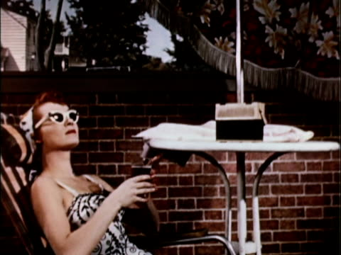 1956 MS Woman in bathing suit and sunglasses sitting on patio lounge chair / USA