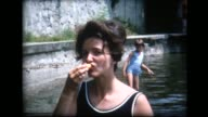 1965 woman in bathing suit takes a bite from bread, then tosses crumb over her shoulder