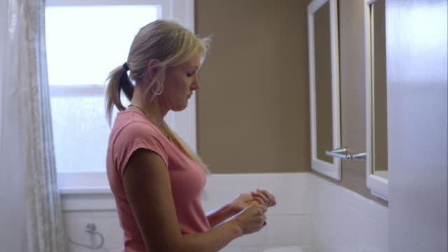 Woman in bathroom getting pill bottle from cabinate taking pill, spilling water on her shirt and laughing.