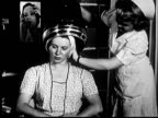 1953 MS woman in beauty parlor with head in hair dryer, chewing gum as she smiles and nods at nurse/ Norman, Oklahoma