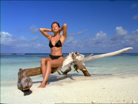 Woman in bikini sitting on driftwood on beach with ocean in background / Seychelles