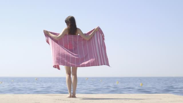 Woman in bikini wrapping towel around on beach