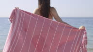 Woman in bikini wrapping towel around