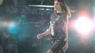 Woman in black dress walking on a catwalk tossing her hair.