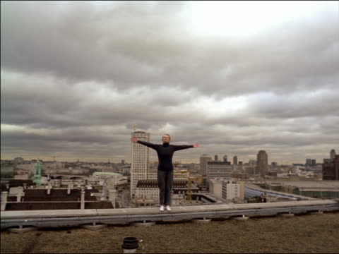 Woman in black standing on edge of roof with arms spread out / London skyline + cloudy sky in background