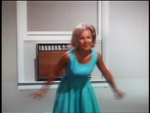1966 woman in blue dress dancing by air conditioners + shaking head in studio / industrial